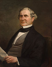 Portrait of older, gray-haired man, seated, holding a piece of paper.
