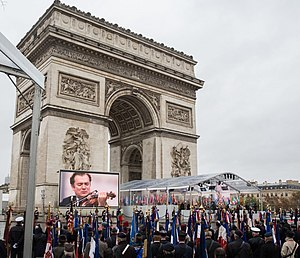 A crowd is around the Arc of Triumph in Paris, France.