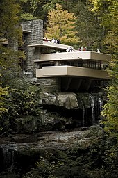 A modernist-style house sits nestled in the woods, with a multilevel terrace hanging over a waterfall