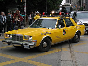 Toronto Police Service - A yellow former Metro Toronto Police car makes an appearance during a parade.