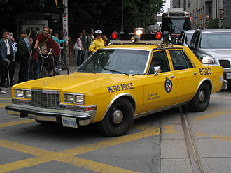 Toronto Police Service - A yellow former Metro Toronto Police car makes an appearance during a parade.