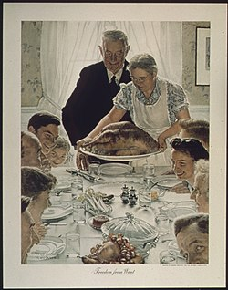 A large family gathered at a table for a holiday meal as the Turkey arrives at the table.