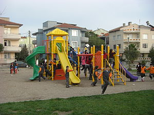 An overcrowded playground in a public garden f...