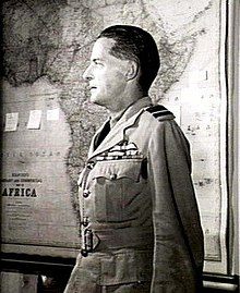 Profile half-portrait of dark-haired man in light-coloured military uniform with map of Africa in background