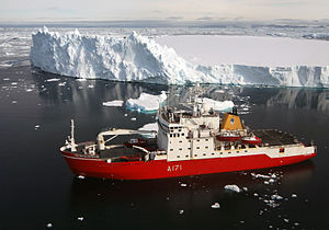 An overhead view of HMS Endurance coloured bright red. About 100 metres from her are icebergs, coloured white. The sea is calm, and a deep blue.