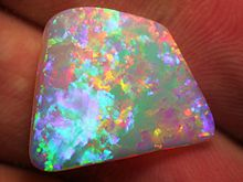 A small, white, trapezoid opal held in someone's hand. Its fire is relatively bright, display a number of finely-grained colours throughout.