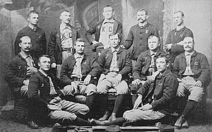 Baseball players are posing for a photograph, five men standing, five men sitting on chairs, and two are sitting on the floor.