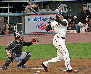 A dark skinned man in a white baseball uniform takes a left-handed baseball swing as a catcher kneels behind him.