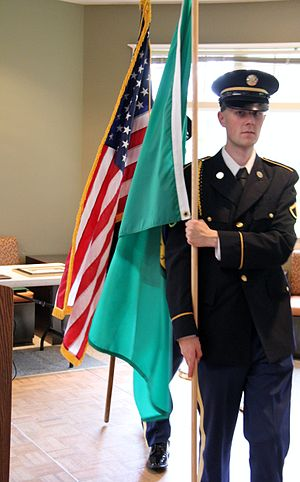 Washington State Guard - A Washington State Guardsman carrying the Washington state flag during a WSG dining event.