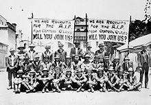 "Black and white group portrait of a group of men wearing suits seated and standing in front of two banners. Both banners read ""We are the recruits for the A.I.F. from Central Q'Land [Queensland] will you join us?"" in block letters."