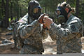 A U.S. Soldier with the 327th Chemical Company, right, assists her battle buddy with drinking water through a protective mask while participating in a decontamination simulation during Exercise Red Dragon 110608-A-VF714-012.jpg