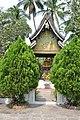 A beautiful Buddha shrine behind the bushes at Wat Xieng Thong (14418891177).jpg