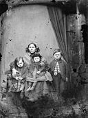 A group of one woman and three children NLW3364660.jpg