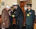 "A service officer from Kendriya Sainik Board pinning a lapel on the Vice President, Shri Mohd. Hamid Ansari, on the occasion of ""Armed Forces Flag Day"", in New Delhi on December 06, 2013.jpg"