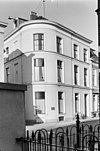 foto van Pand, dat de afrondende linkerhoek vormt van een in het derde kwart van de 19e eeuw als een symmetrisch geheel ontworpen straatwand