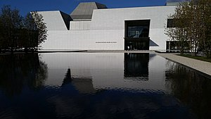 Aga Khan Museum - The front of the museum is reflected in a square black stone reflecting pond