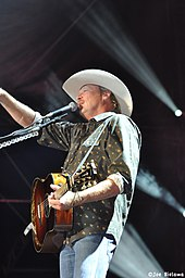 A fair-haired man wearing a white cowboy hat, a green shirt and blue jeans, playing a guitar and singing into a microphone