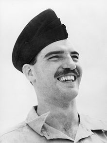 Informal head-and-shoulders portrait of grinning moustachioed man in forage cap