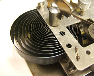 Mainspring - Mainspring in a 1950s alarm clock. The end of the spring is attached to the frame post at lower right.