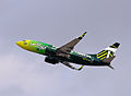 Left side view of a mostly-green aircraft with Portland Timbers colors taking off in clear skies