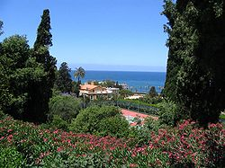 Varied foliage and flowers in the foreground the landscape slopes downward toward a tennis court and buildings lying near the coast