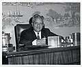 An unidentified man holds a pen while sitting at the mayor's desk (12461585765).jpg