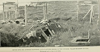 Brevig Mission, Alaska - Native huts and storage platforms, with platform graves in the distance, Teller reindeer station (1894)