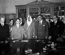 Five men standing side-by-side behind a table with documents on it. All the men are wearing suits and ties, with the exception of the man in the middle, who is wearing a traditional robe and headdress. There are three men standing behind them.