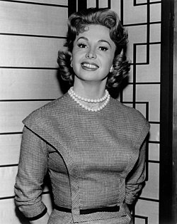 a woman wearing a pearl necklace and pin-striped dress stands in the corner with her hands behind her