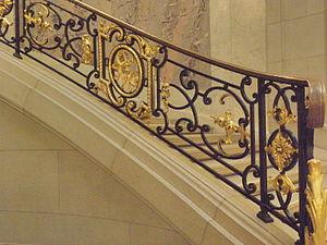 photographie d'une rampe d'escalier en fer forgé et en partie doré