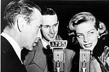 Lauren Bacall in black and white with Humphrey Bogart speaking into microphones