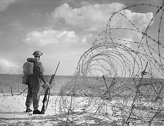 Devon and Cornwall County Division - An infantryman, standing among an example of British anti-invasion beach defences, looks out over the English Channel.