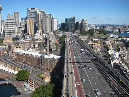 The roadway of the bridge, from the southern or city approach. From left: walkway, eight traffic lanes (the two leftmost once carried the Sydney trams), two railway tracks, and cycleway. The gantries with lights controlling traffic tidal flow are clearly visible, while the tollbooths can be seen near the bases of the high-rise buildings Cahill expressway from bridge.jpg