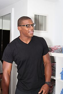 A man wearing glasses and a black shirt.