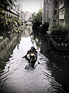 Canoeists paddle down one of the tranquil canals of Ghent.jpg