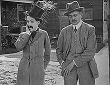 Capture d'écran montrant deux hommes en costume dans une rue. Chaplin porte un haut-de-forme, une redingote et la moustache tombante.
