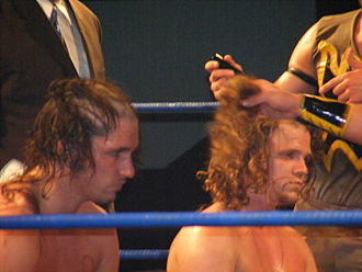 Icarus (wrestler) - Chuck Taylor and Icarus having their heads shaved after losing a Double Mask vs. Double Hair match against The Colony