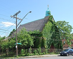 "An ivy-covered building with a pointed roof and a small green dome with a cross seen from across a street, with a car parked in front. There is a chainlink fence around it and the ground slopes downwards towards its rear. A street sign at the corner reads ""Colonie"" and ""North Pearl""."