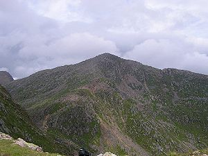 The side of a mountain covered with purple heather and green vegetation. The background is filled with blue-grey, puffy clouds.