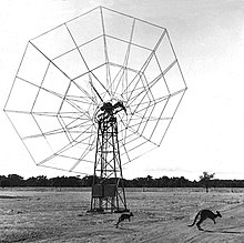 "Monochrome photo of a lightly constructed, web-like ""dish"" antenna in a flat paddock, with two kangaroos leaping across the foreground"