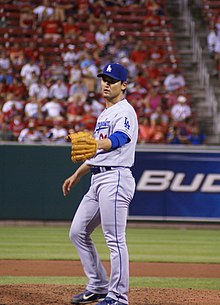 A man wearing a gray baseball uniform and blue baseball cap extends his baseball-gloved left hand.