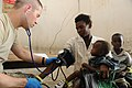 Defense.gov News Photo 100430-A-1526R-065 - U.S. Army Sgt. Tommy Fenton left a medic with 94th Combat Support Hospital out of Seagoville Texas listens to the heart rate of a Haitian.jpg