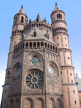 The apsidal end of a tall red stone church framed by circular towers.