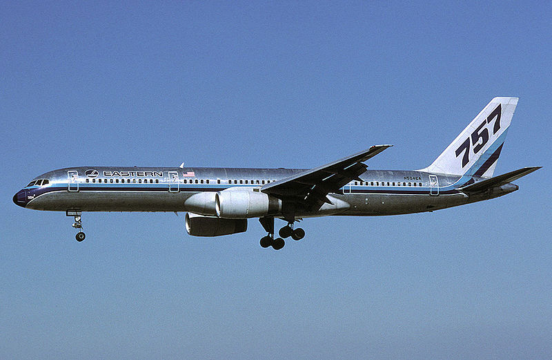 "Side view of silver twinjet in flight, with ""757"" markings on tail."