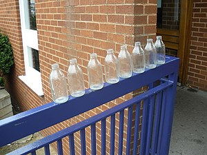 English: Eight milk bottles .....outside Exmou...
