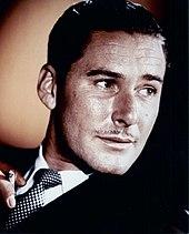 Portrait en couleur, Flynn fume une cigarette et a la tête tournée vers la droite.