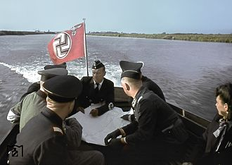 Reich Ministry of Transport - RVM State Secretary Albert Ganzenmüller (Center, with map) overseeing the construction of a railway bridge with his staff on the Dnieper River, Russia, July 1943.