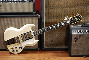 Music technology (electric) - A 1963 Gibson SG Custom electric guitar with its headstock leaning on a small guitar amplifier, which contains a power amplifier and a loudspeaker in a wooden cabinet.