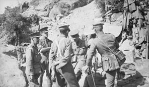 Six men in uniform with peaked caps satand and sit in a circle talking to each other. In the background are sandbags, tins and clothing hung out to dry.