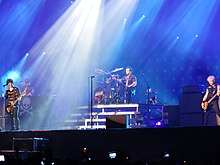 A color photograph of members of the group Green Day on stage with instruments